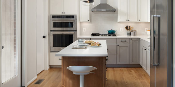 Renovated kitchen with white countertops, gray and white cabienets, and stainless steel appliances