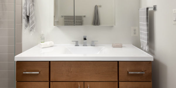 Remodeled Bathroom with white countertops and wooden cabinets