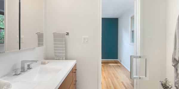 bathroom remodeling project featuring white countertops and wooden cabinets