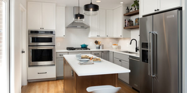 Remodeled kitchen with wooden flooring, stainless steel appliances, and white cabinets