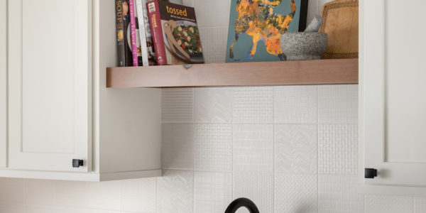 Over the sink shelving for books and plants in a remodeled kitchen