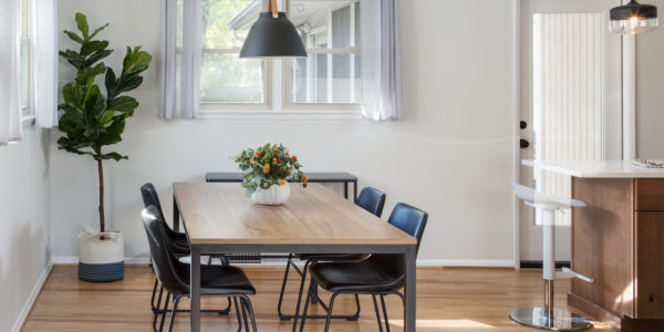 Renovated kitchen with pale wood floors and table and industrial style furniture