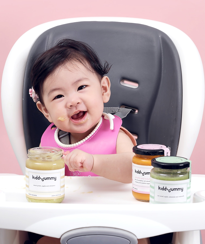 Asian baby girl sitting on chair having Kiddyummy meal