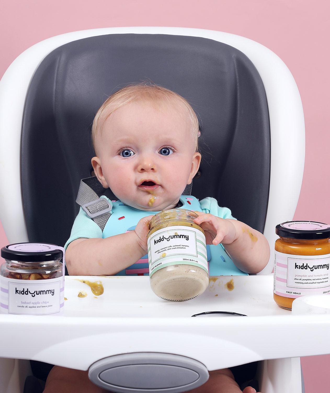 Western baby boy sitting on chair having Kiddyummy meal