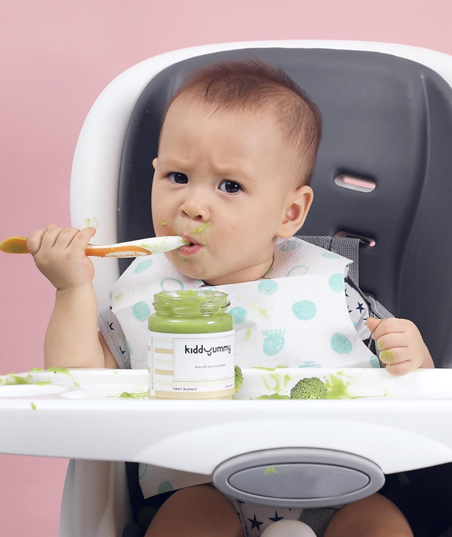 Asian baby boy sitting on chair having Kiddyummy meal