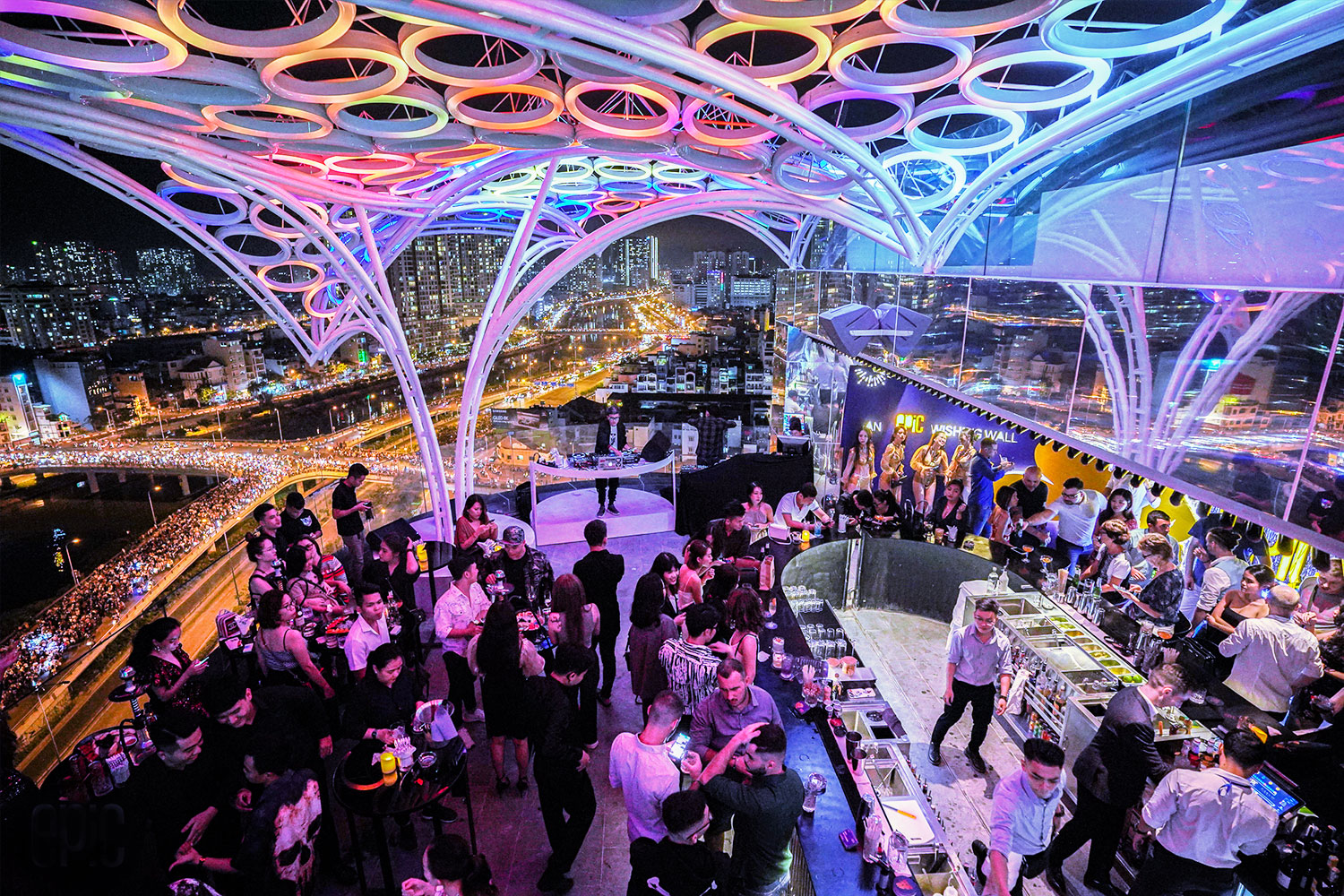 People dancing under vibrant light on epic sky lounge rooftop