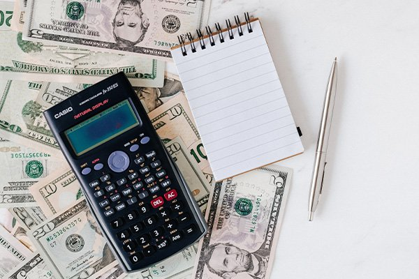 cash and calculator with notepad and pen