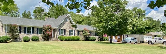 Photo of ranch brick home with pitch gable over main family area of the home. The 7H Roofing and Construction trucks are parked to the side of the home and the roofing materials have been delivered and are stacked in the driveway.