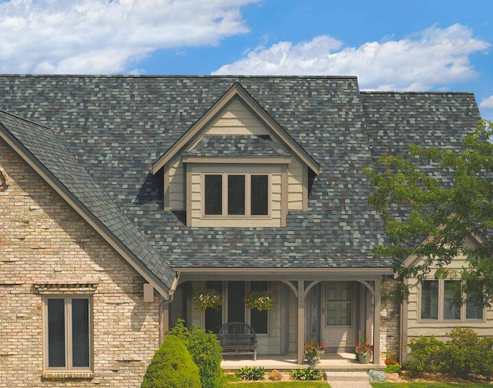 photo of blue hardi sided home with entry dormers and steep pitched roofline. The architectural dark slate roof sets off the blue of the exterior of the home.