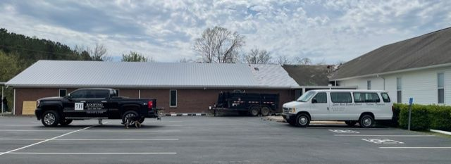 Photo of Solid Rock Baptist Church showing the installation of the Old Town Grey Metal roof partially installed. You can see the underlay for the metal roof. The sanctuary still sports the old asphalt roof