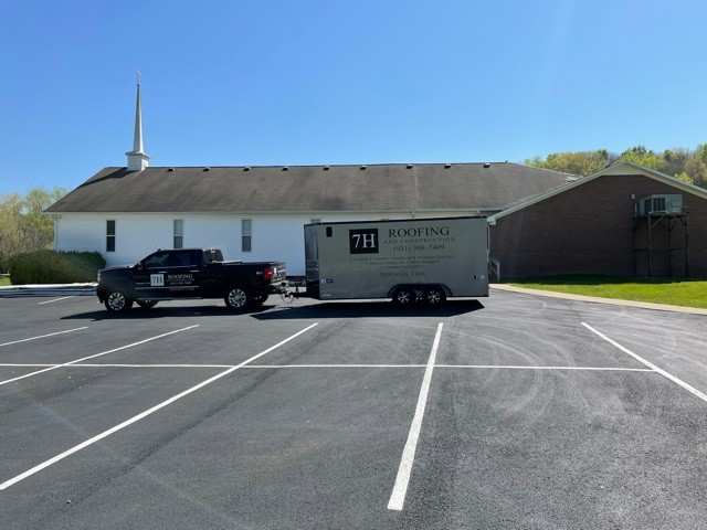 Photo of the 7H Roofing trailer in the parking lot of Solid Rock Baptist Church. the project is just about to begin to replace a dark and stained black asphalt roof with an Old Town Grey metal roof