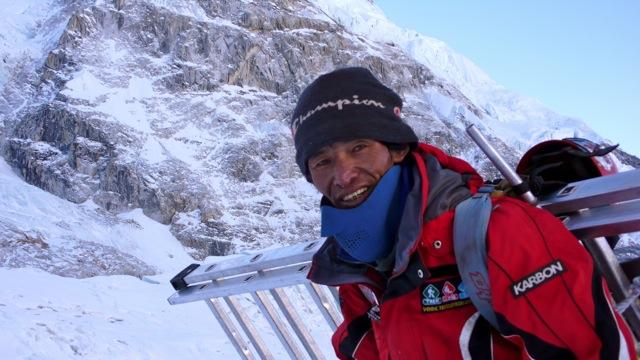 A Man Climbing Up a Snowy Mountain
