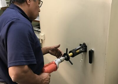 Technician drilling a safe