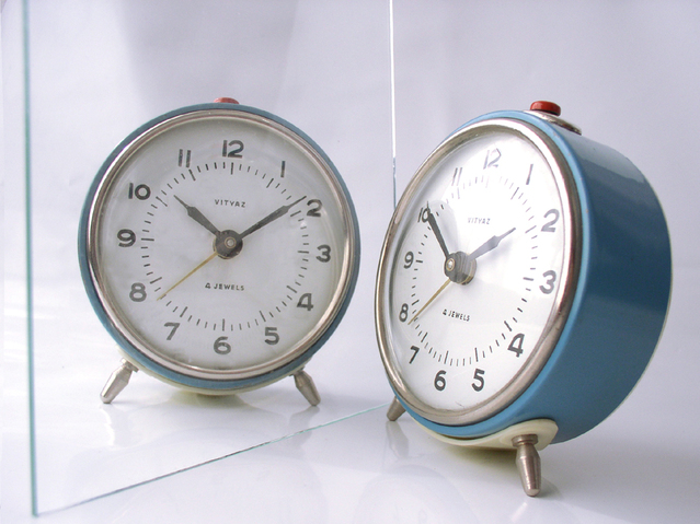 Vintage blue alarm clock and its mirror image