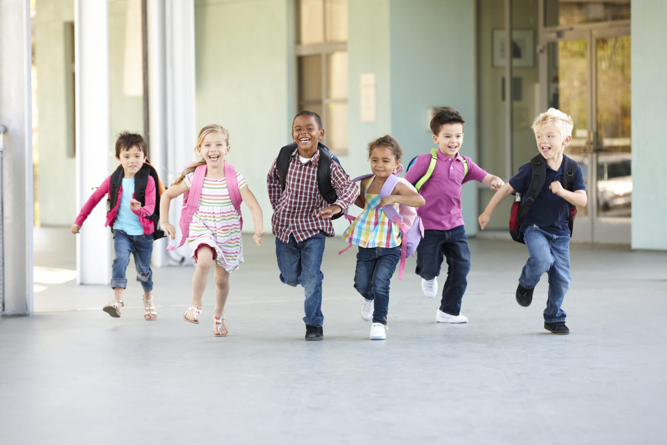 Group Of Elementary Age Schoolchildren Running Outside
