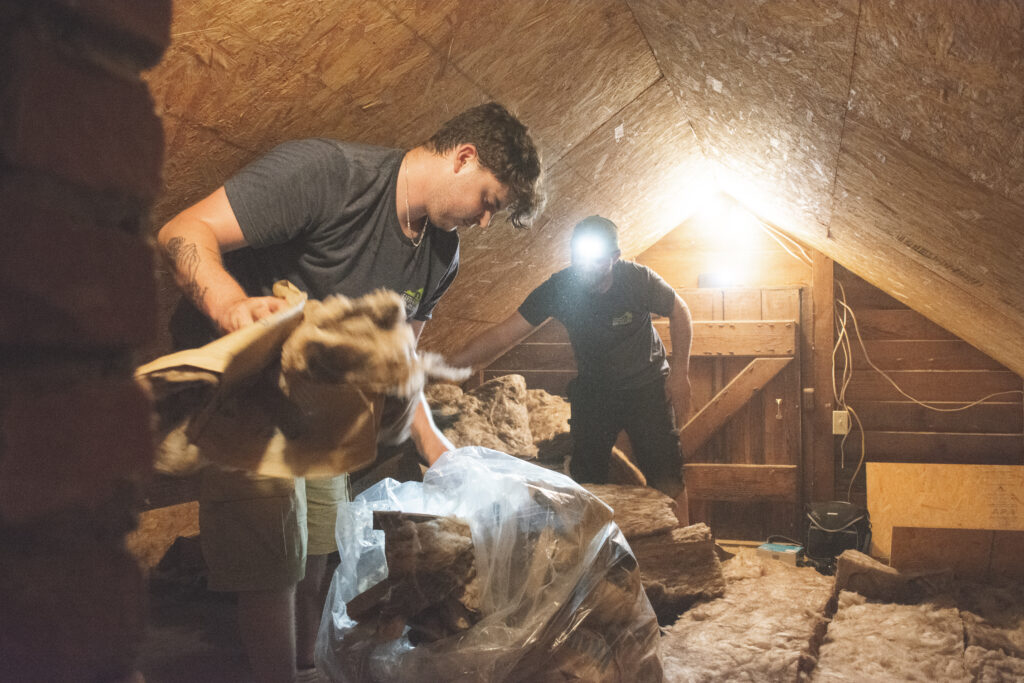 Installers installing insulation in an attic
