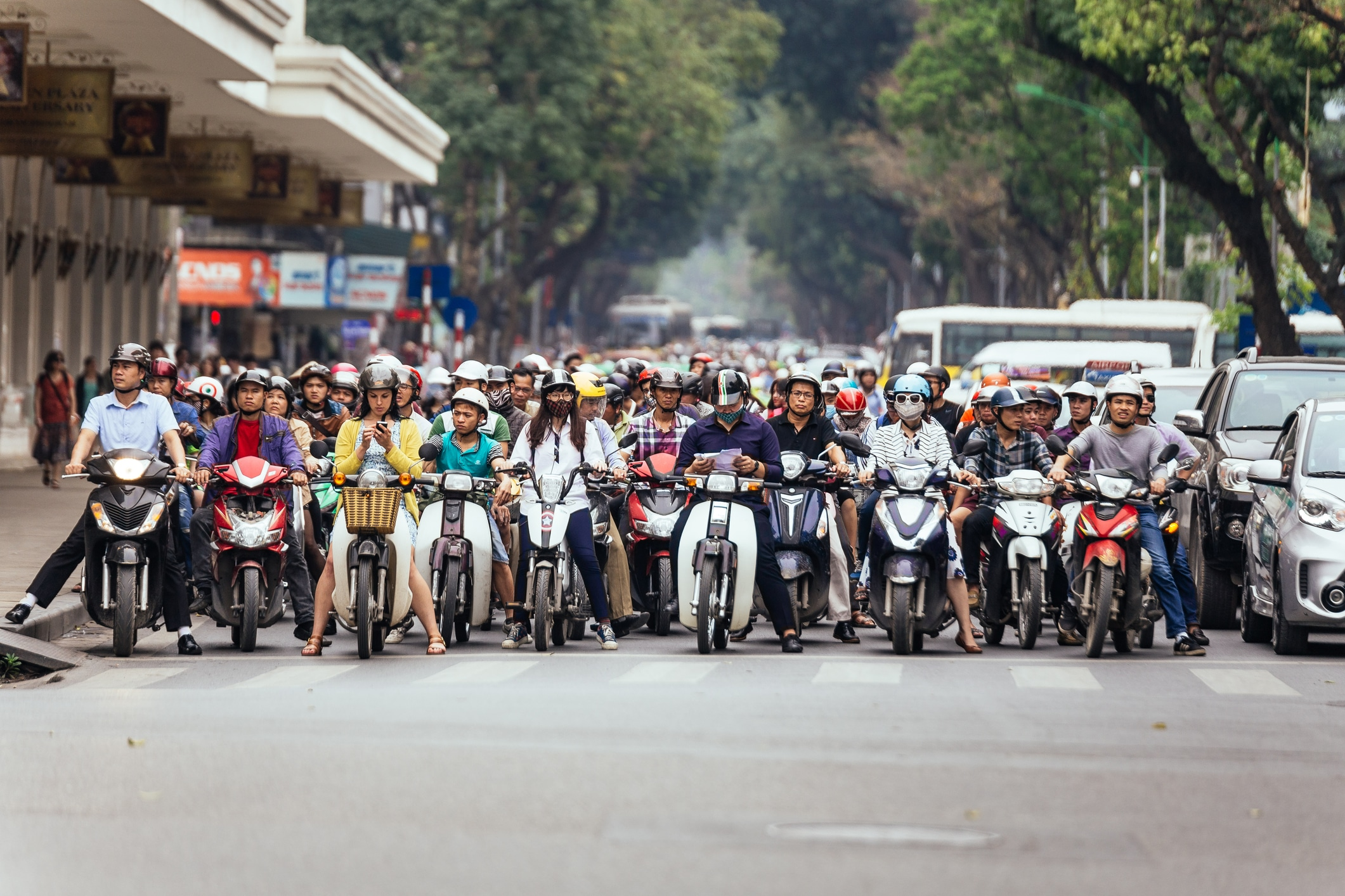 Motorcycles got traffic jam on the road with green trees in background at Hanoi, Vietnam.