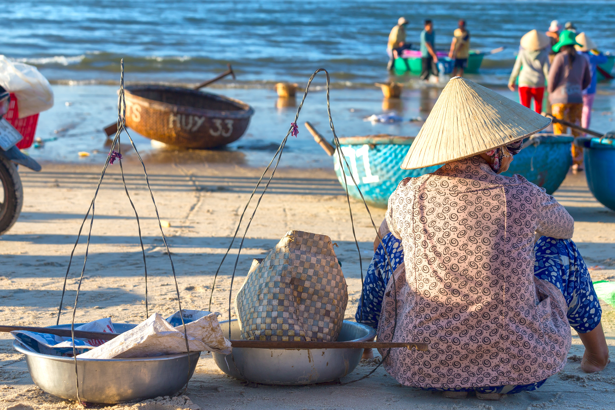 Binh Thuan, Vietnam - January 21st, 2016: Woman with shoulder alignment is waiting for fishermen to bring the beach to buy fish for sale in the morning market in the fishing village of Binh Thuan, Vietnam
