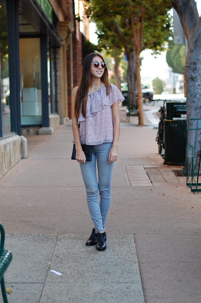 one shoulder gray jeans crossed