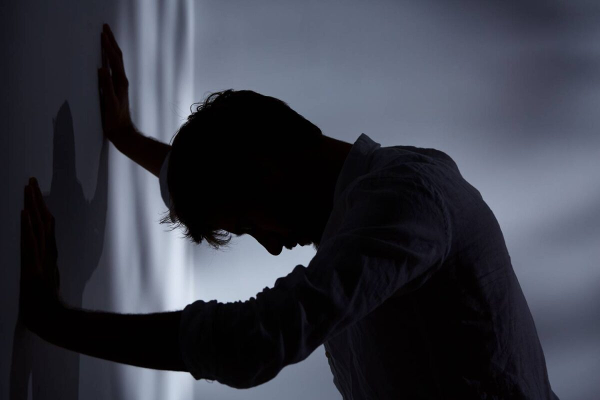 A person struggling with substance use leans against a wall