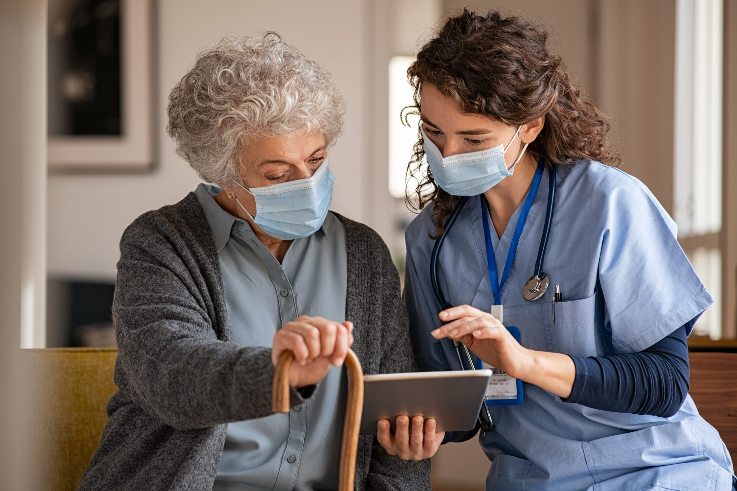 Young doctor and senior woman going through medical record on digital tablet during home visit wearing face protective mask. Old woman holding walking cane sitting with nurse while listen to the covid-19 therapy. Mature woman with doctor wearing surgical mask and using digital tablet during coronavirus pandemic.