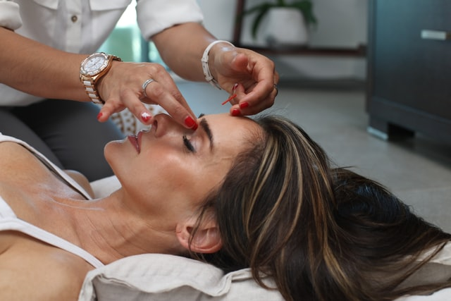 A professional skincare expert administers botox injections to another woman's forehead