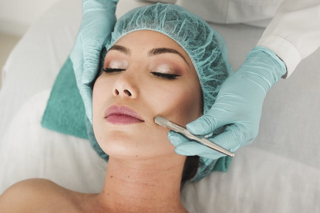 A woman receives a skin-care treatment from a professional wearing rubber gloves