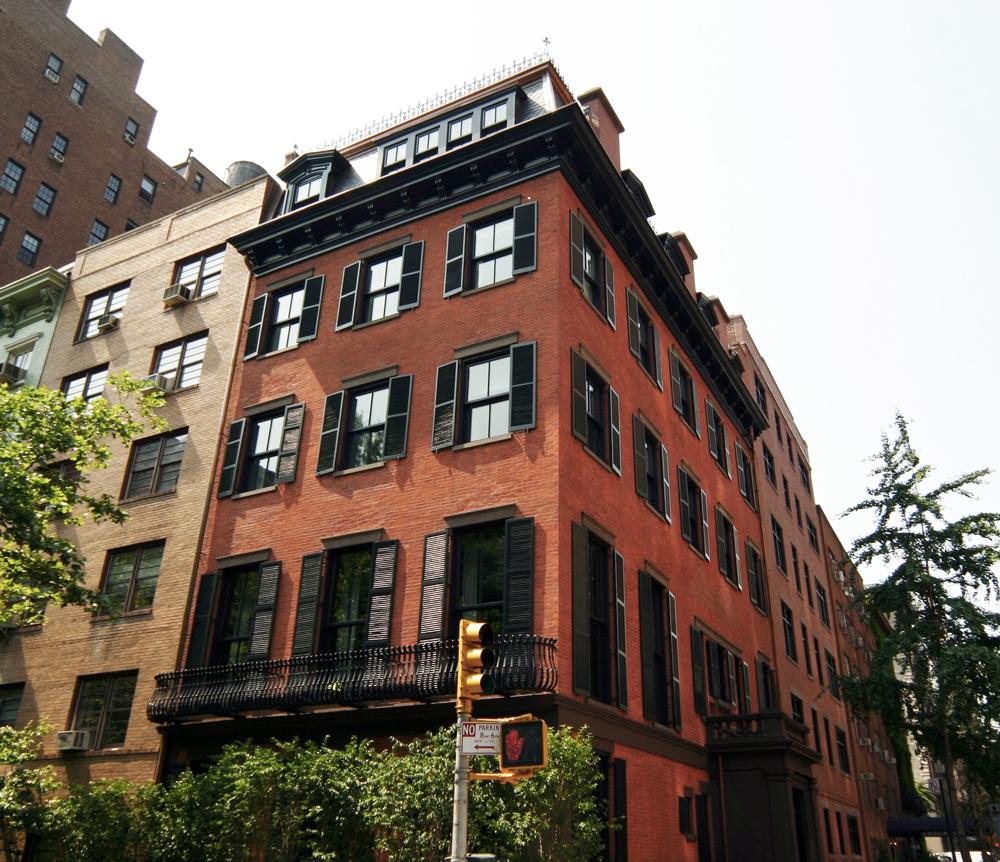 Corner façade of a three-story, bricked apartment building