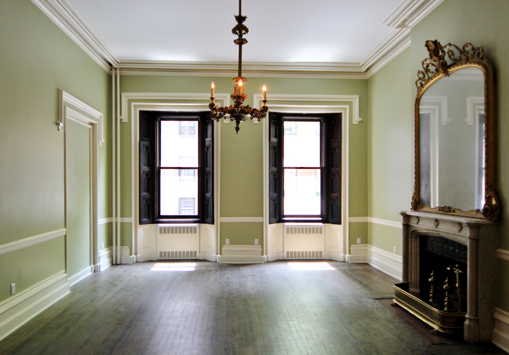 Lime-green colored empty room with two windows, a chandler, and a fireplace with a mirror above it