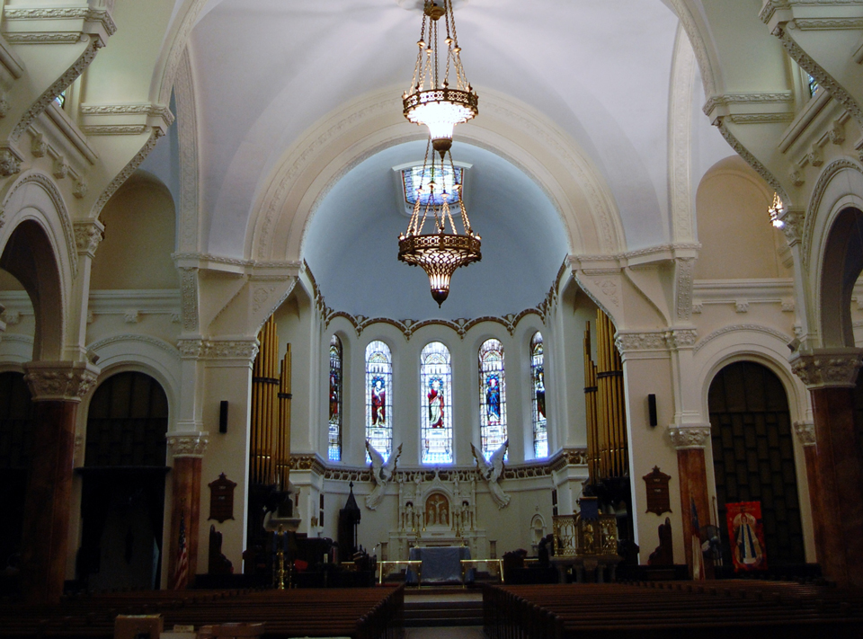 Interior center of a church with a chandler that has church pews leading up to the altar
