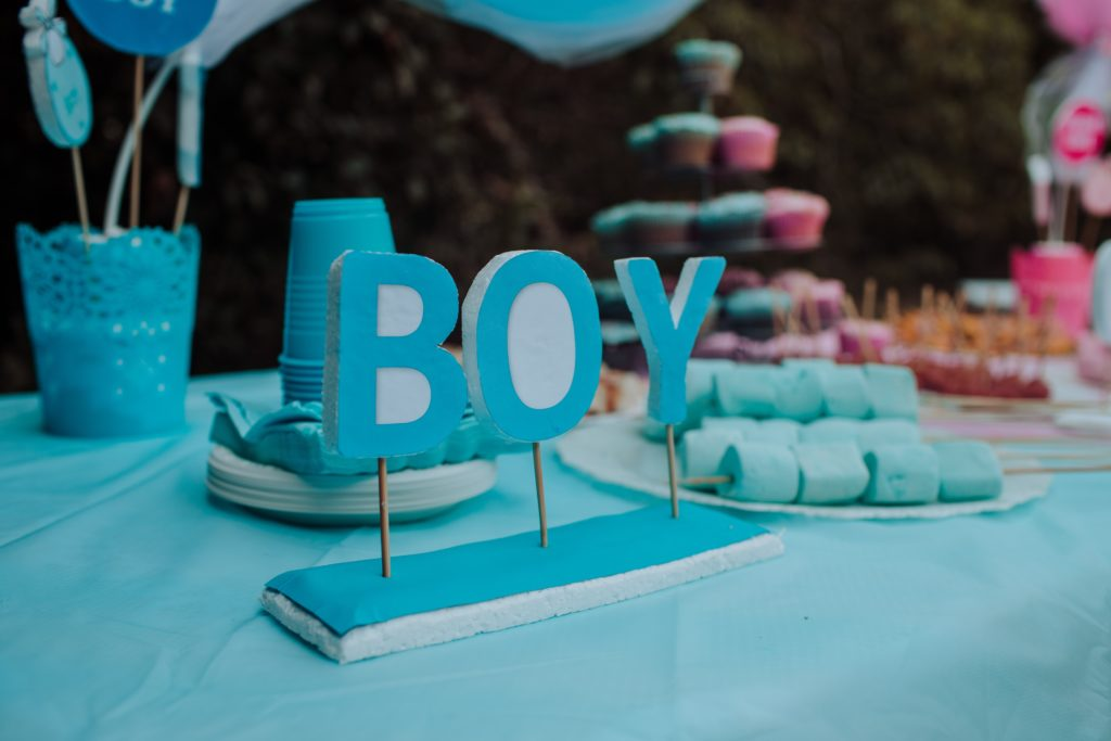 """Table covered with blue decorations and treats with a sign saying """"BOY."""""""