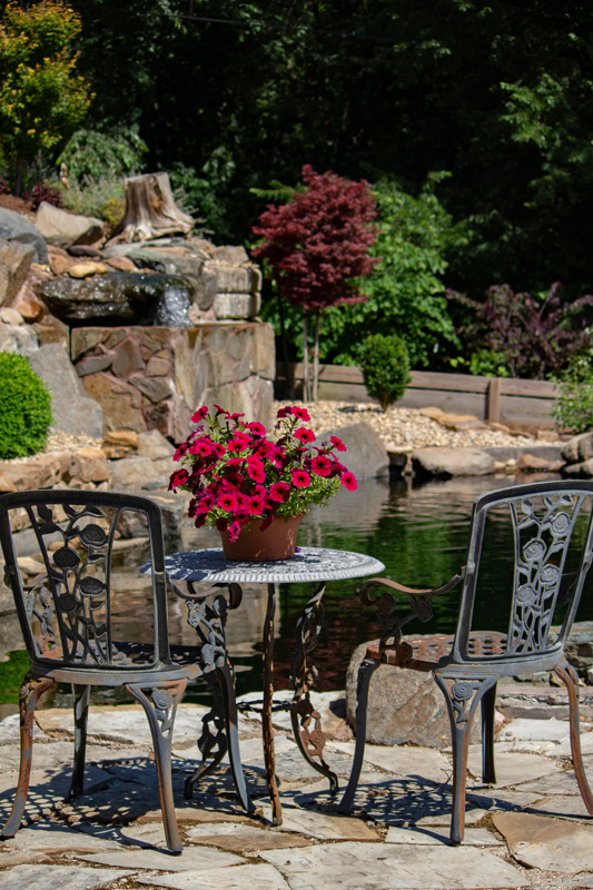 Two chairs on a flagstone patio overlooking a pond with a waterfall in the background.