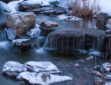 winterized pond with waterfalls and boulders