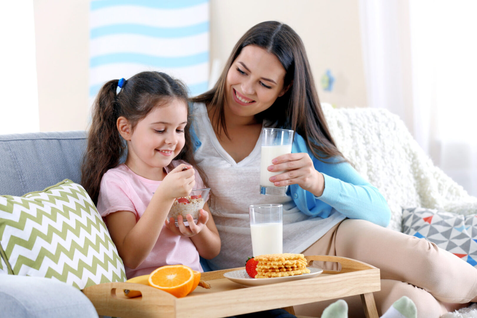 Mother,And,Daughter,Having,Healthy,Breakfast,On,Sofa,In,Room