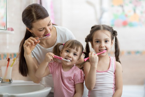 family brushing teeth together