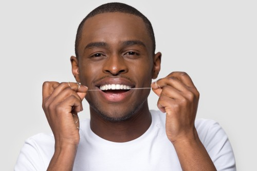 man flossing teeth