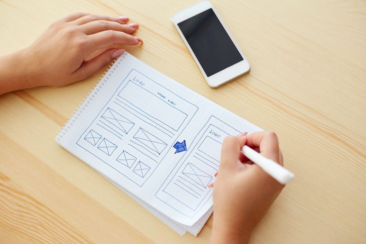 A web developer sketching out a responsive website design
