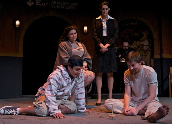 Louis Farber (in background), Meg Sullivan (standing), and Andrea Morales (in chair) watch, from left, Marcelino Quiñonez and Tyler Eglen in memory, in The Last Days of Judas Iscariot. (Photo by John Groseclose)