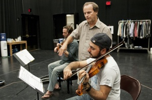 """Jim Apperson coaches Pasha Yamotahari on how to properly bow a violin during a rehearsal for Actors Theatre's """"Opus."""" (Photo by Molly J. Smith, Arizona Republic)"""
