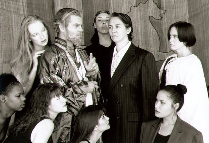 """Suze St. John (in suit) as the King of Naples was one of many male roles essayed by women in Planet Earth Theatre's gender-bending 1996 production of """"The Tempest."""" (Photo from the collection of Mollie Kellogg)."""