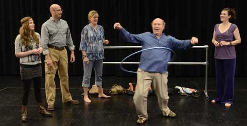 David demonstrates his skill with the hula hoop while his castmates watch. (Photo by John Groseclose.)