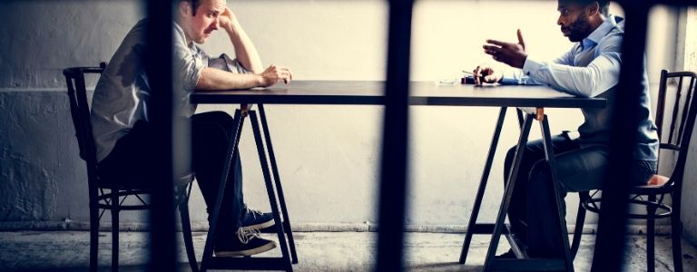 two men sitting across table criminal law fargo