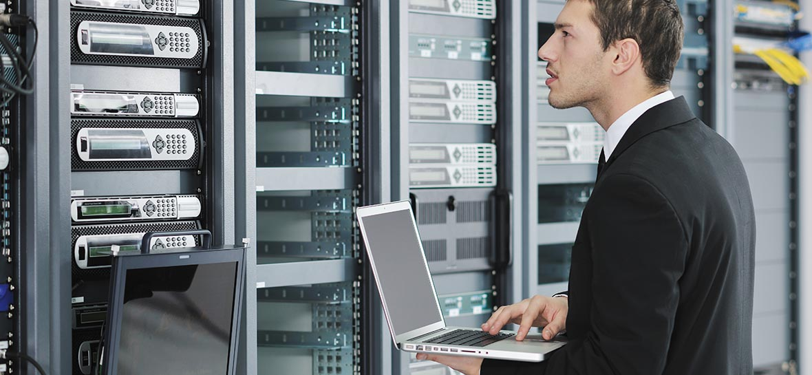 young engineer business man with thin modern aluminium laptop in network server room