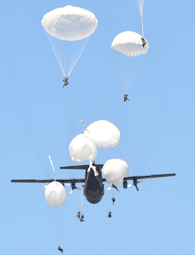 A C-130 plane drops paratroopers from the Polish 6th Airborne Division during a multi-national jump with soldiers and equipment from the U.S., Great Britain and Poland on to a designated drop zone near Torun, Poland, Tuesday, June 7, 2016. The exercise, Swift Response-16, sets the stage in Poland for the multi-national land force training event Anakonda-16. (AP Photo/Alik Keplicz)
