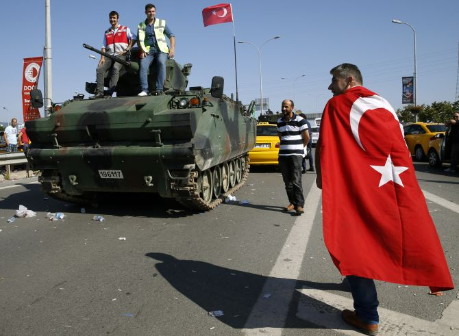 A man wrapped in a Turkish flag walks past a military vehicle in front of Sabiha Airport, in Istanbul, Turkey July 16, 2016. REUTERS/Baz Ratner - RTSI8VV
