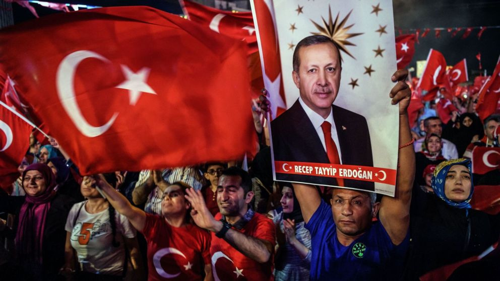 Pro-Erdogan supporters hold Turkish national flags and a portrait of Turkish President Recep Tayyip Erdogan during a rally against the military coup on Taksim square in Istanbul on July 23, 2016. Turkey pushed on with a sweeping crackdown against suspected plotters of its failed coup, defiantly telling EU critics it had no choice but to root out hidden enemies. Using new emergency powers, President Recep Tayyip Erdogan's cabinet decreed that police could now hold suspects for one month without charge, and also announced it would shut down over 1,000 private schools it deems subversive. / AFP / OZAN KOSE (Photo credit should read OZAN KOSE/AFP/Getty Images)