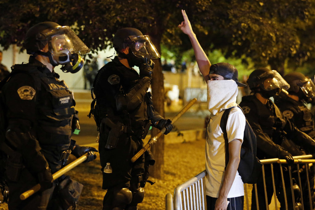 Riot police block off the Albuquerque Convention Center to anti-Trump protests following a rally and speech by Republican presidential candidate Donald Trump at the convention center where the event was held, in Albuquerque, N.M., Tuesday, May 24, 2016. (AP Photo/Brennan Linsley)