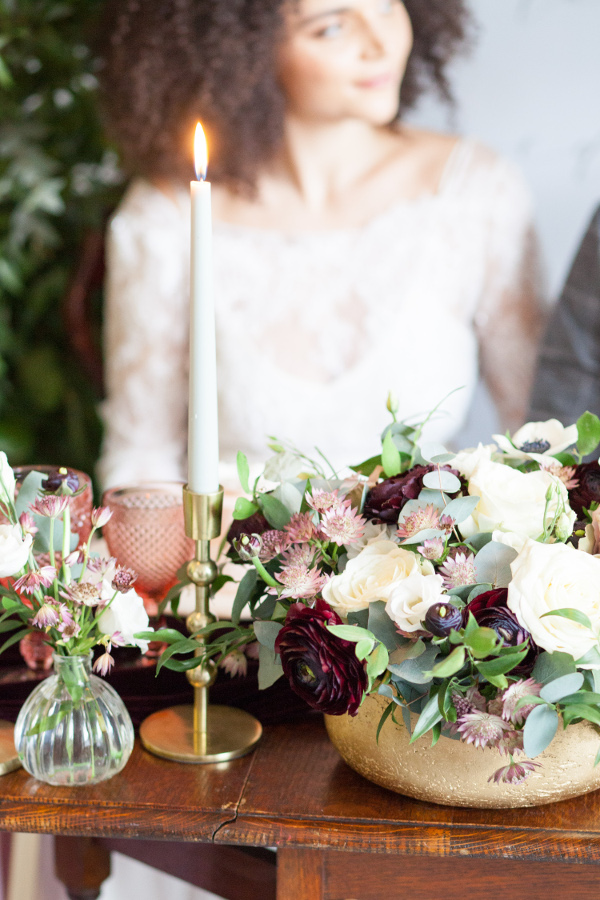 Candle, flowers and bride sitting at sweetheart table image