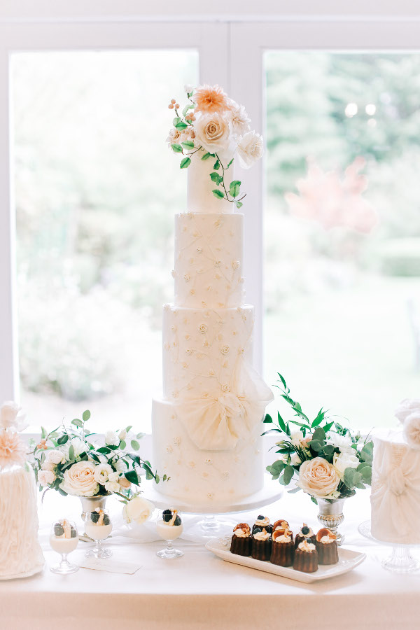 4 tier wedding cake with fresh flowers and bow detailing