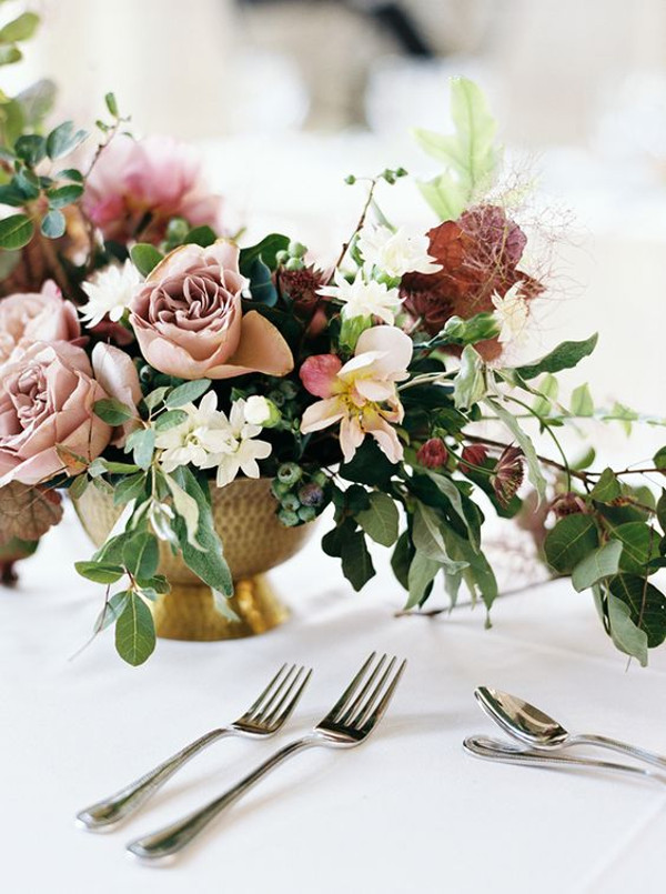 Wedding table centrepiece in a bronze vase with shades of blush, burgundy